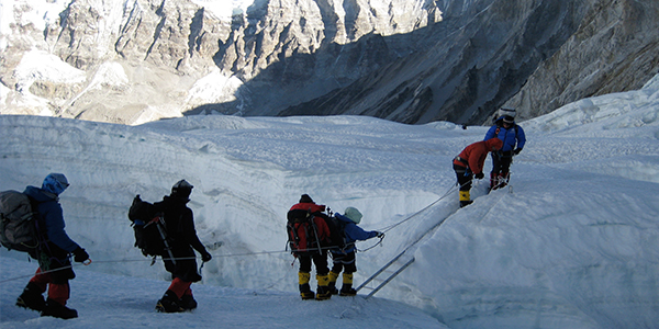 Climbers crossing a crevasse on Everest (Photo credit: Triump of the Spirit)